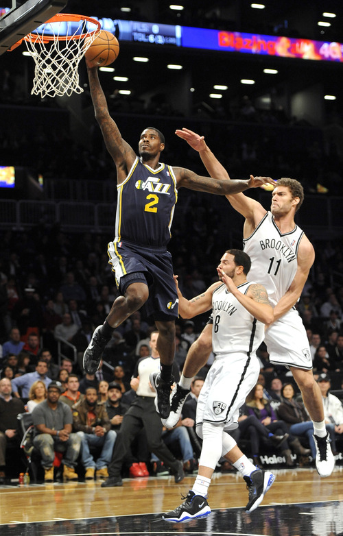Utah Jazz's Marvin Williams (2) drives to the basket in front of Brooklyn Nets' Deron Williams (8) and Brook Lopez (11) in the first half of an NBA basketball game, Tuesday, Dec. 18, 2012, at Barclays Center in New York. (AP Photo/Kathy Kmonicek)