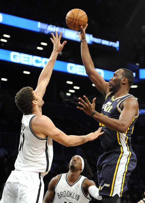 Utah Jazz's Al Jefferson (25) shoots over Brooklyn Nets' Brook Lopez (11) and Gerald Wallace (45) in the first half of an NBA basketball game, Tuesday, Dec. 18, 2012, at Barclays Center in New York. (AP Photo/Kathy Kmonicek)