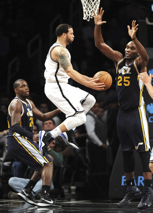 Brooklyn Nets' Deron Williams leaps for a shot between Utah Jazz's Paul Millsap (24) and Al Jefferson (25) in the first half of an NBA basketball game, Tuesday, Dec. 18, 2012, at Barclays Center in New York. (AP Photo/Kathy Kmonicek)