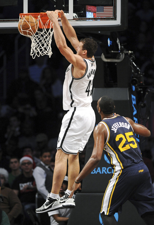 Brooklyn Nets' Kris Humphries (43) dunks in front of Utah Jazz's Al Jefferson (25) in the first half of an NBA basketball game, Tuesday, Dec. 18, 2012, at Barclays Center in New York. (AP Photo/Kathy Kmonicek)
