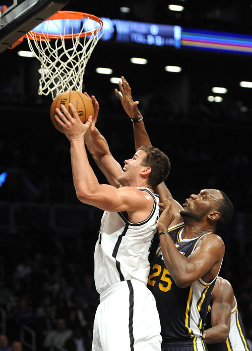 Utah Jazz's Al Jefferson (25) blocks the shot of Brooklyn Nets' Kris Humphries (43) in the second half of an NBA basketball game, Tuesday, Dec., 18, 2012, at Barclays Center in New York. The Jazz won 92-90. (AP Photo/Kathy Kmonicek)