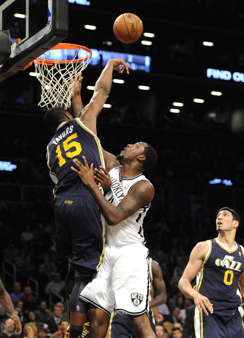 Utah Jazz's Derrick Favors (15) blocks the shot of Brooklyn Nets' Andray Blatche (0) in the second half of an NBA basketball game, Tuesday, Dec., 18, 2012, at Barclays Center in New York. The Jazz won 92-90. (AP Photo/Kathy Kmonicek)
