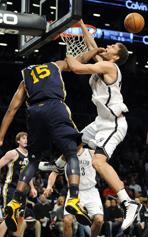 Brooklyn Nets' Brook Lopez (11) is hit in the face by Utah Jazz's Derrick Favors (15) during the second half of an NBA basketball game, Tuesday, Dec. 18, 2012, at Barclays Center in New York. The Jazz won 92-90. (AP Photo/Kathy Kmonicek)