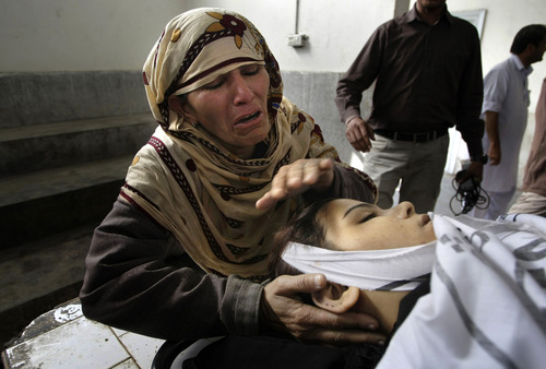 Rukhsana Bibi mourns over the body of her daughter, polio worker Madiha Bibi, killed by unknown gunmen, at the morgue of local hospital in Karachi, Pakistan, Tuesday, Dec. 18, 2012. Gunmen killed several people working on a government polio vaccination campaign in two different Pakistani cities on Tuesday, officials said. The attacks were likely an attempt by the Taliban to counter an initiative the militant group has long opposed. (AP Photo/Fareed Khan)