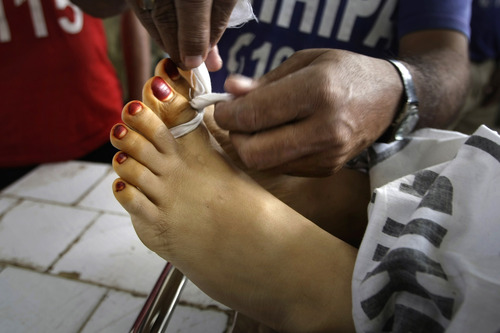 A Pakistani hospital worker ties together the toes of Madiha Bibi, a polio worker killed by unknown gunmen, at the morgue of a local hospital in Karachi, Pakistan, Tuesday, Dec. 18, 2012. Gunmen killed several people working on a government polio vaccination campaign in two different Pakistani cities on Tuesday, officials said. The attacks were likely an attempt by the Taliban to counter an initiative the militant group has long opposed. (AP Photo/Fareed Khan)