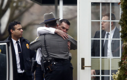 Police officers comfort one another outside a funeral service for 6-year-old Noah Pozner, Monday, Dec. 17, 2012, in Fairfield, Conn. Pozner was killed when a gunman walked into Sandy Hook Elementary School in Newtown Friday and opened fire, killing 26 people, including 20 children. (AP Photo/Jason DeCrow)