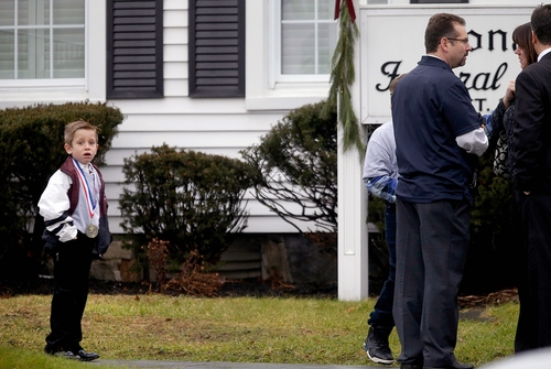 A young boy looks on as mourners arrive for the funeral service of Sandy Hook Elementary School shooting victim, Jack Pinto, 6, Monday, Dec. 17, 2012, in Newtown, Conn. Pinto was killed when a gunman walked into Sandy Hook Elementary School in Newtown Friday and opened fire, killing 26 people, including 20 children.(AP Photo/David Goldman)