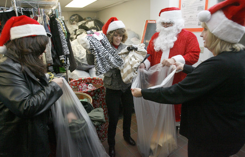 Francisco Kjolseth  |  The Salt Lake Tribune Bank of Utah volunteers, Patty Frehner, Kelly Johnson, Craig Roper A.K.A Santa and Mary Ryan sort through barrels of coats, blankets, and other warm items they had just delivered to the Crossroads Urban Center Thrift Store on Wednesday, December 19, 2012. Donations made to three Bank of Utah branches, including customer cash donations, matched by the bank for a total of $1000.
