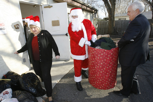 Francisco Kjolseth  |  The Salt Lake Tribune Bank of Utah volunteers Mary Ryan, Doug DeFries and Craig Roper A.K.A Santa, carry barrels of coats, blankets, and other warm items they had just delivered to the Crossroads Urban Center Thrift Store on Wednesday, December 19, 2012. Donations made to three Bank of Utah branches, including customer cash donations, matched by the bank for a total of $1000 were delivered to the center.