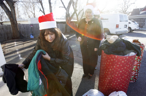 Francisco Kjolseth  |  The Salt Lake Tribune Bank of Utah volunteers Patty Frehner, Mary Ryan and Kelly Johnson, from left, carry coats, blankets, and other warm items they had just delivered to the Crossroads Urban Center Thrift Store on Wednesday, December 19, 2012. Donations made to three Bank of Utah branches, including customer cash donations, matched by the bank for a total of $1000 were delivered to the center.