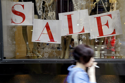"""In this Tuesday, Dec. 18, 2012, photo, a person passes a retail store with sale sign displayed in the window in Philadelphia. When it comes to big discounts, better late than never. This holiday shopping season, stores haven't been offering the same big discounts as they did in previous years as they tried to lure shoppers in with other incentives,but during the final days leading up to Christmas, shoppers will see more of those jaw-dropping """"70 percent off"""" sale signs as stores try to salvage a season that so far has been disappointing.  (AP Photo/Matt Rourke)"""