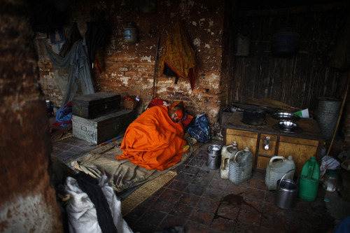 A Hindu holy man takes a nap after morning chores near the Pashupatinath Temple in Katmandu, Nepal, Wednesday, Dec. 19, 2012. The Pashupatinath Temple, located on the banks of the Bagmati River, is one of the most revered temples of Lord Shiva, the Hindu god of death and destruction. (AP Photo/Niranjan Shrestha)