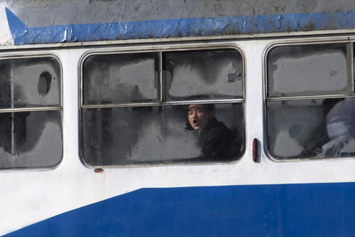 A North Korean man blows onto the frosted window of a tram in Pyongyang, North Korea, Wednesday, Dec. 19, 2012. (AP Photo/Ng Han Guan)