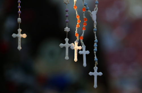 Rosaries are lit by the morning light on a makeshift memorial near the town Christmas tree in the Sandy Hook village of Newtown, Conn., Wednesday, Dec. 19, 2012. The memorial, which was put up in the aftermath of the elementary school shooting that shocked the small town, is increasing in size as the days go on. More funerals are scheduled for Wednesday, as the town continues to mourn its victims. The gunman, Adam Lanza, walked into Sandy Hook Elementary School in Newtown, Conn., on Dec. 14, and opened fire, killing 26 people, including 20 children, before killing himself. (AP Photo/Julio Cortez)