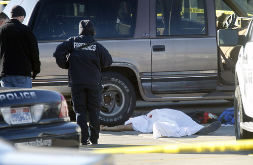 Al Hartmann  |  The Salt Lake Tribune Forensics experts investigate crime scene on the north side parking lot of Work Force Services at 5680 South Redwood Road where a Unified police officer shot and killed a man who was attacking a woman with a knife in a brown SUV Thursday morning December 20.
