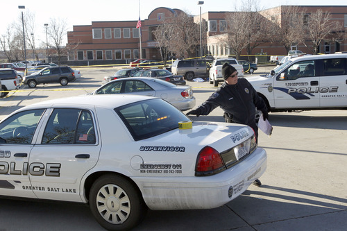 Al Hartmann  |  The Salt Lake Tribune Unified Police investigate a crime scene on the north side parking lot of Workforce Services at 5680 South Redwood Road where a Unified police officer shot and killed a man who was attacking a woman in a brown SUV.