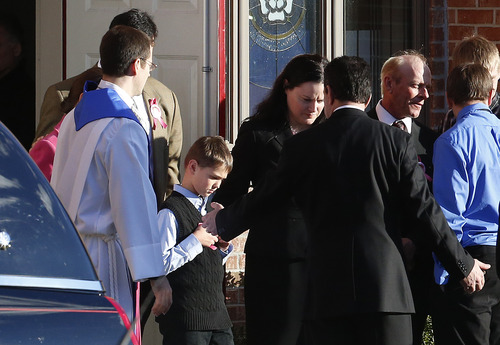 Guy Bacon, center, walks with family members out of Christ the King Lutheran Church following funeral services for his sister, Charlotte Helen Bacon, one of the students killed in the Sandy Hook Elementary School shooting, Wednesday, Dec. 19, 2012, in Newtown, Conn. The gunman, Adam Lanza, walked into Sandy Hook Elementary School in Newtown, Conn. on Dec. 14 and opened fire, killing 26 people, including 20 children, before killing himself. (AP Photo/Julio Cortez)