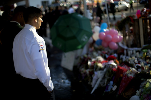 Area firefighters visit a memorial to the Sandy Hook Elementary School shooting victims outside the school's entrance before the funeral procession for 7-year-old Daniel Gerard Barden, Wednesday, Dec. 19, 2012, in Newtown, Conn.  Barden was killed when Adam Lanza walked into Sandy Hook Elementary School in Newtown, Conn., Dec. 14, and opened fire, killing 26 people, including 20 children, before killing himself. (AP Photo/David Goldman)
