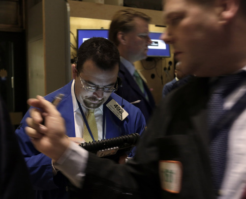 """FILE - Trader Richard Scardino, left, works on the floor of the New York Stock Exchange, in this Dec. 14, 2012 file photo taken in in New York. World stock markets faced resistance Thursday Dec. 20, 2012 after talks turned sour among U.S. political leaders trying to reach an agreement over how to avert an economically disastrous """"fiscal cliff"""" before the end of the year. A downturn in U.S. housing starts also hurt sentiment.  (AP Photo/Richard Drew, File)"""