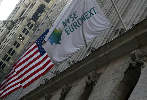Flags fly on the facade of the New York Stock Exchange Thursday, Dec. 20, 2012. Shares in the company that runs the New York Stock Exchange are surging amid reports that it is in talks to sell itself to a rival stock exchange, Atlanta-based IntercontinentalExchange Inc. (AP Photo/Richard Drew)