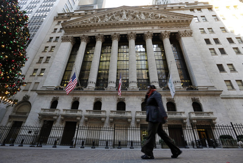 A woman walks by the New York Stock Exchange Thursday, Dec. 20, 2012. Shares in the company that runs the New York Stock Exchange are surging amid reports that it is in talks to sell itself to a rival stock exchange, Atlanta-based IntercontinentalExchange Inc. (AP Photo/Richard Drew)