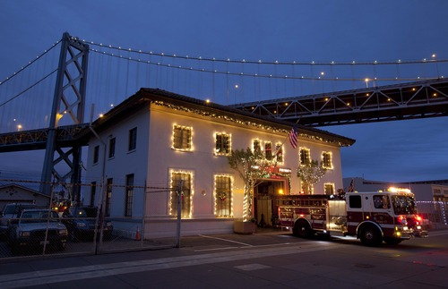 In this photo taken Tuesday, Dec. 4, 2012 a firehouse along the Embarcadero is lit up with Christmas lights in San Francisco. In the background is the San Francisco-Oakland Bay Bridge. San Francisco's fireboats are also housed at the station. (AP Photo/Eric Risberg)