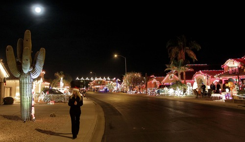 In this Saturday, Dec. 1, 2012 photo, a woman walks along Natal Circle viewing Christmas lights in Gilbert, Ariz. (AP Photo/Matt York)