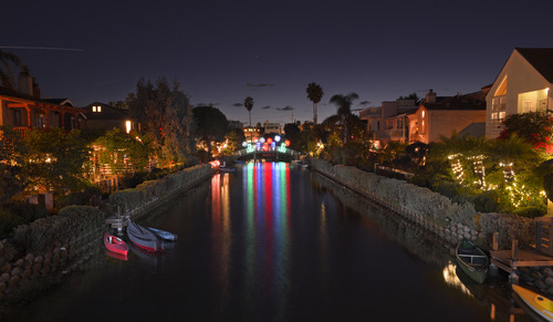 In this Thursday, Dec. 13, 2012 photo holiday lights from a bridge are reflected in the canal waters in the Venice section of Los Angeles. (AP Photo/Mark J. Terrill)