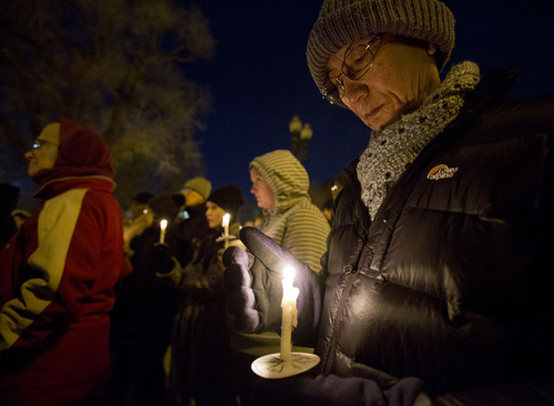 Lennie Mahler  |  The Salt Lake Tribune Rev. Eun-sang Lee, pastor of The First United Methodist Church of Salt Lake City, observes a moment of silence at a vigil remembering the homeless people who have died and recognizing the struggles members of the homeless population face heading into Winter. The event, organized by the Fourth Street Clinic and the Salt Lake County Homeless Coordinating Council, was held at Pioneer Park and is part of a nationwide event on the eve of the Winter Solstice. Thursday, Dec. 20, 2012.