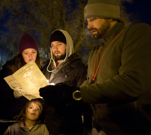 Lennie Mahler  |  The Salt Lake Tribune Cat Rogers, left, Levi Rogers, Joel Hunt and Alidia Cox, bottom, read The Traveler's Prayer at a vigil in memorial of the homeless people who have died and recognizing the struggles members of the homeless population face heading into Winter. The event, organized by the Fourth Street Clinic and the Salt Lake County Homeless Coordinating Council, was held at Pioneer Park and is part of a nationwide event on Thursday on the eve of the Winter Solstice.