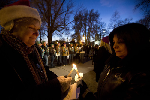 Lennie Mahler  |  The Salt Lake Tribune Pam Lloyd and Carolyn DeHerrera, members of Volunteer for America, light candles at a vigil remembering the homeless people who have died and recognizing the struggles members of the homeless population face heading into Winter. The event, organized by the Fourth Street Clinic and the Salt Lake County Homeless Coordinating Council, was held at Pioneer Park and is part of a nationwide event on the eve of the Winter Solstice. Thursday, Dec. 20, 2012.