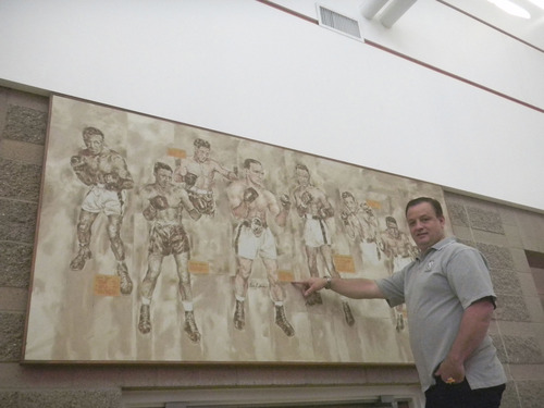 Tom Wharton  |  The Salt Lake Tribune Gene Fullmer Recreation Center Director Brad Pitcher stands in front of a signed mural by local artist Ev Thorpe showing former middleweight champion Gene Fullmer and the men he fought for the title. The Fullmer family recently donated the mural and other memorabilia to the West Jordan recreation center.