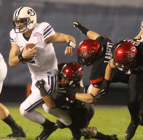 Rick Egan  | The Salt Lake Tribune   Brigham Young Cougars quarterback James Lark (7) is tackled for a loss on third down, in football action during the Poinsettia Bowl, BYU vs. San Diego State, Thursday, December 20, 2012.