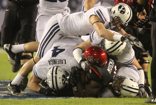 Rick Egan  | The Salt Lake Tribune   It takes four Brigham Young Cougars to bring down San Diego State Aztecs running back Adam Muema (4) in football action during the Poinsettia Bowl, BYU vs. San Diego State, Thursday, December 20, 2012.