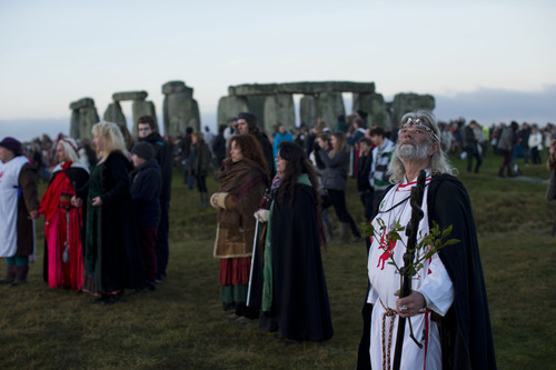 "Druid leader Arthur Uther Pendragon, right, looks up as people face east to watch the sunrise by the ancient stone circle of Stonehenge, in southern England, as access to the site is given to druids, New Age followers and members of the public on the annual Winter Solstice, Friday, Dec. 21, 2012.  Doomsday hour is here and so still are we.  According to legend, the ancient Mayans' long-count calendar ends at midnight Thursday, ushering in the end of the world. Didn't happen.  ""This is not the end of the world. This is the beginning of the new world,"" Star Johnsen-Moser, an American seer, said at a gathering of hundreds of spiritualists at a convention center in the Yucatan city of Merida, an hour and a half from the Mayan ruins at Chichen Itza.  (AP Photo/Matt Dunham)"