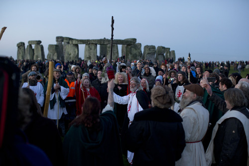 "Druid leader Arthur Uther Pendragon, center, holds up his staff as he takes part in a ceremony before sunrise by the ancient stone circle of Stonehenge, in southern England, as access to the site is given to druids, New Age followers and members of the public on the annual Winter Solstice, Friday, Dec. 21, 2012.  Doomsday hour is here and so still are we. According to legend, the ancient Mayans' long-count calendar ends at midnight Thursday, ushering in the end of the world. Didn't happen.  ""This is not the end of the world. This is the beginning of the new world,"" Star Johnsen-Moser, an American seer, said at a gathering of hundreds of spiritualists at a convention center in the Yucatan city of Merida, an hour and a half from the Mayan ruins at Chichen Itza. (AP Photo/Matt Dunham)"