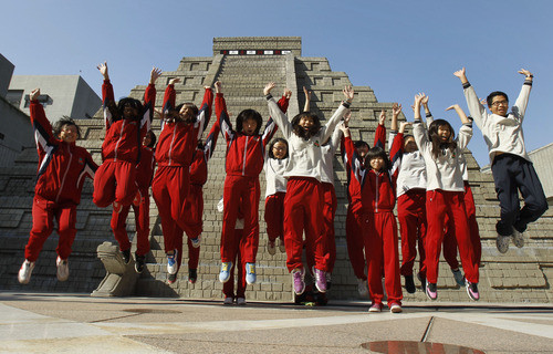 Students jump together to pose for photographers in front of a mock pyramid after the countdown time when many believe the Mayan people predicted the end of the world, Friday, Dec. 21, 2012, in Taichung, southern Taiwan. (AP Photo/Wally Santana)