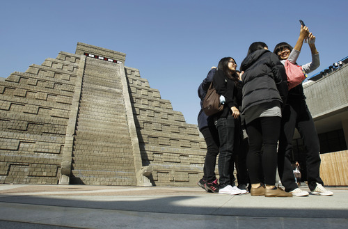 Students take pictures of themselves in front of a mock pyramid during the countdown to when many believe the Mayan people predicted the end of the world, Friday, Dec. 21, 2012, in Taichung, southern Taiwan. (AP Photo/Wally Santana)