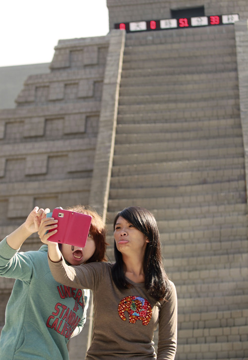 Two women take pictures of themselves in front of a mock pyramid during the countdown to when many believe the Mayan people predicted the end of the world, Friday, Dec. 21, 2012, in Taichung, southern Taiwan. (AP Photo/Wally Santana)