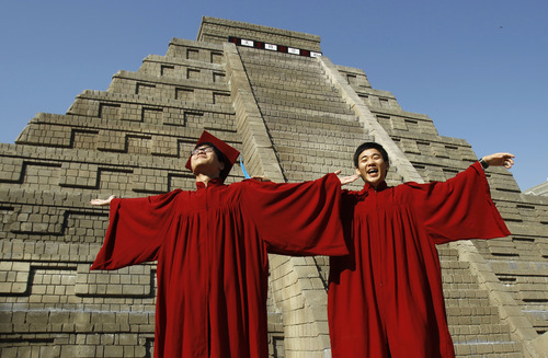 Students dressed in graduation gowns pose in front of a mock pyramid moments before the countdown time when many believe the Mayan people predicted the end of the world, Friday, Dec. 21, 2012, in Taichung, southern Taiwan. (AP Photo/Wally Santana)
