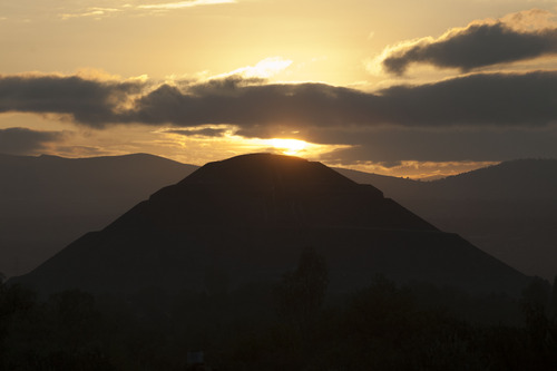 The sun rises behind the Pyramid of the Sun at the Teotihuacan archeological site in Teotihuancan, Mexico, Friday, Dec. 21, 2012. Many believe today is the conclusion of a vast, 5,125-year cycle in the Mayan calendar. Some have interpreted the prophetic moment as the end of the world, while others as believed it marked the birth of a new and better age. (AP Photo/Alexandre Meneghini)