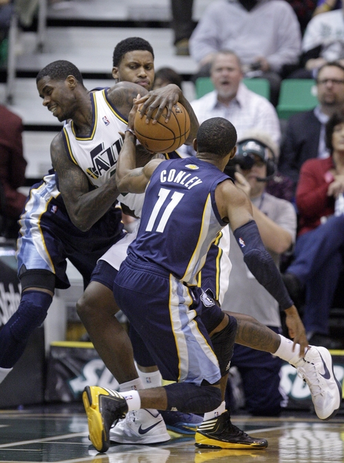 Utah Jazz point guard Earl Watson (11) reaches for the ball as Utah Jazz power forward Marvin Williams drives to the basket as Memphis Grizzlies small forward Rudy Gay, behind, looks on in the first quarter during an NBA basketball game on Saturday, Dec. 15, 2012, in Salt Lake City. (AP Photo/Rick Bowmer)