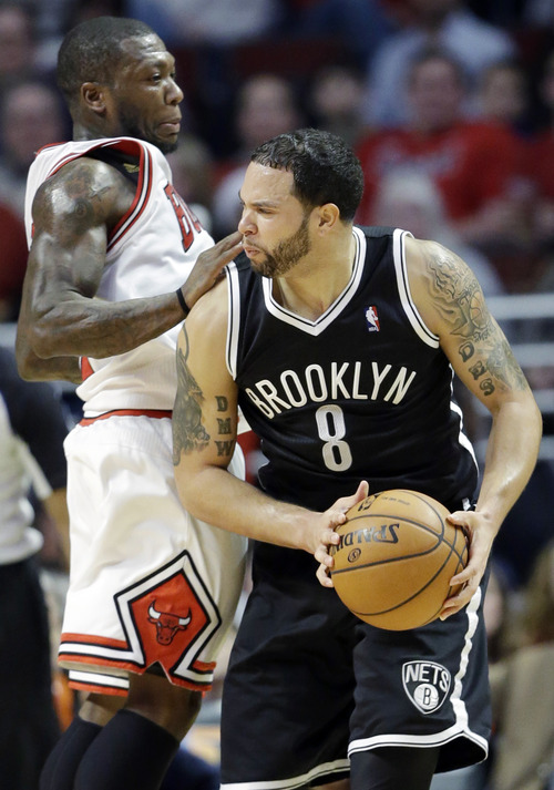 Brooklyn Nets guard Deron Williams, right, looks to a pass as Chicago Bulls guard Nate Robinson guards during the second half of an NBA basketball game in Chicago on Saturday, Dec. 15, 2012. The Bulls won 83-82. (AP Photo/Nam Y. Huh)