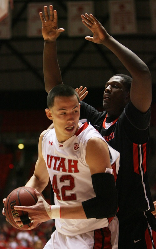Kim Raff  |  The Salt Lake Tribune University of Utah center Jason Washburn (42) tries to drive the basket as he is defended by (right) Cal State Northridge center Brandon Perry (32) during a game at the Huntsman Center in Salt Lake City on December 21, 2012.