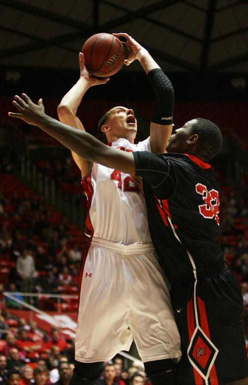 Kim Raff  |  The Salt Lake Tribune (left) University of Utah center Jason Washburn (42) shoots the ball as Cal State Northridge center Brandon Perry (32) defends during a game at the Huntsman Center in Salt Lake City on December 21, 2012.