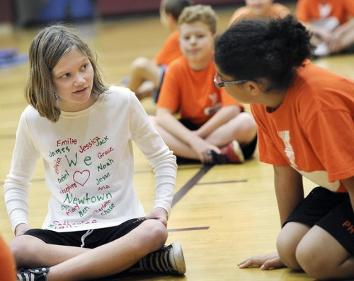 York Suburban Middle School 6th grader Adrianna Pinto, left, talking to classmate Allyssa Klin, wears a shirt with the names of the victims of the Newtown shootings,  Friday, Dec. 21, 2012 in York, Pa.. (AP Photo/York Daily Record, Jason Plotkin)  YORK DISPATCH OUT
