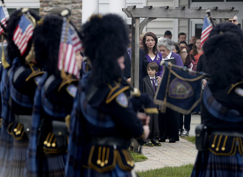 Bagpipers play as Nicole Hockley, center, and her son Jake Hockley look on at the end of a funeral service for Dylan Hockley in Bethel, Conn., Friday, Dec. 21, 2012. Hockley, 6, was killed when Adam Lanza walked into Sandy Hook Elementary School in Newtown, Conn., Dec. 14, and opened fire, killing 26 people, including 20 children, before killing himself. (AP Photo/Seth Wenig)