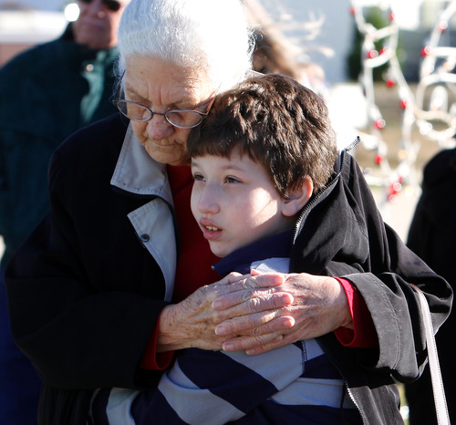 Effie Asproudis holds her grandson, Logan, 10, during a memorial bell-ringing service on Friday, Dec. 21, 2012, at the Gautier Veterans Tribute Tower for those that were killed in last week's shooting at Sandy Hook Elementary in Connecticut. The event was planned following a proclamation by Gov. Phil Bryant for a state-wide moment of silence. (AP Photo/The Sun Herald, Amanda McCoy) TV OUT; MANDATORY CREDIT: MISSISSIPPI PRESS OUT; LOCAL TV OUT WLOX, LOCAL ONLINE OUT; GULFLIVE.COM OUT