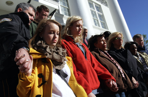 From left, Gulfport, Miss., Police Deputy Chief Leonard Papania, Haley Derouen of Biloxi, Miss., and other South Mississippi residents gather in front of City Hall in Gulfport, Miss. on Friday Dec. 21, 2012 to remember the victims of a mass shooting in Newtown, Conn. last week. Mississippi Gov. Phil Bryant has issued a proclamation calling for a statewide moment of silence in remembrance of the victims of last week's massacre at a school in Connecticut. (AP Photo/Sun Herald, John Fitzhugh)
