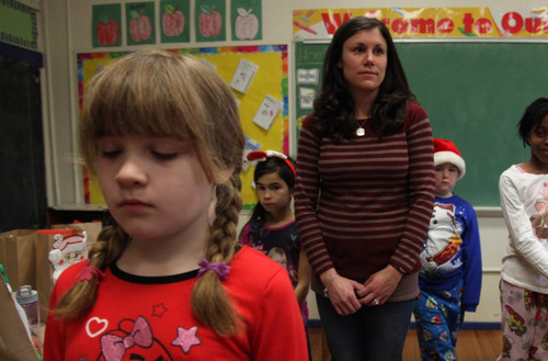 Veronica Burns, left, stands for a moment of silence in Jacquelyn Mansfield's second grade class at Euclid Elementary School in Hasbrouck Heights, N.J. to honor the victims of the Sandy Hook Elementary School shootings, Friday, Dec. 21, 2012. (AP Photo/The Record of Bergen County, Tariq Zehawi) ONLINE OUT; MAGS OUT; TV OUT; INTERNET OUT;  NO ARCHIVING; MANDATORY CREDIT